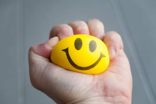 Stress ball wih a smiley face on it being squeezed